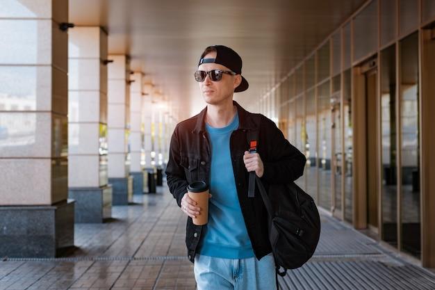 Jonge hipster-man staat op een straat in de stad in een zwarte pet, met een zonnebril op met een kopje koffie