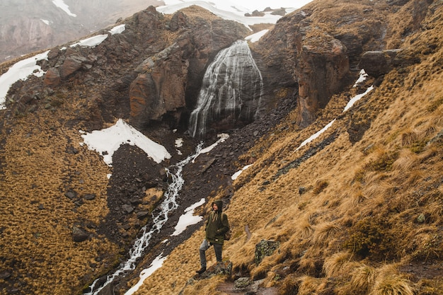 Jonge hipster man wandelen in de bergen, herfstvakantie reizen