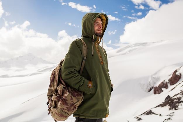 Jonge hipster man wandelen in de bergen, wintervakantie reizen