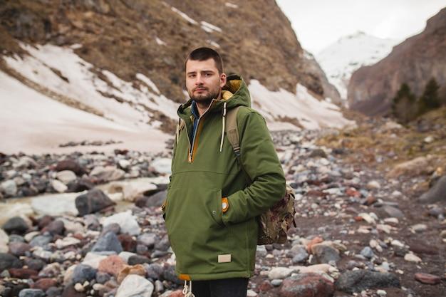 Jonge hipster man wandelen langs de rivier, wilde natuur, wintervakantie