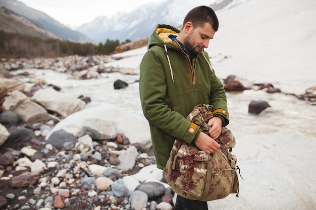 Jonge hipster man, wilde natuur, wintervakantie, wandelen