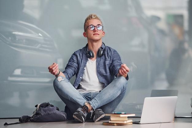 Jonge hipster man zit binnenshuis met laptop en boeken