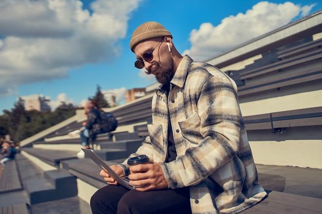 Jonge hipster man zit buiten met koffie terwijl bloggers op het werk naar muziek of webinar luisteren