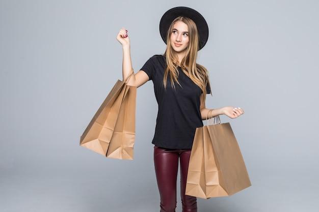 Jonge hipster meisje gekleed in t-shirt en lederen broek met lege ambachtelijke boodschappentassen met handvatten geïsoleerd op wit
