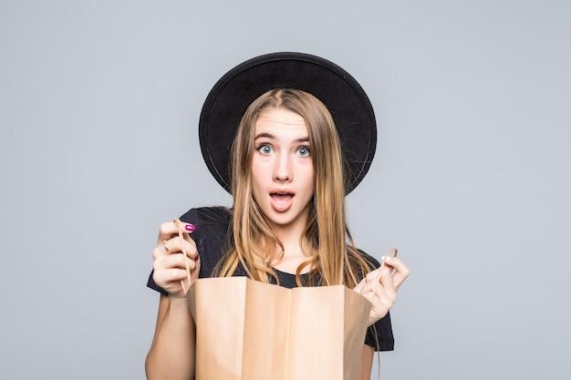 Jonge hipster meisje gekleed in zwart t-shirt en lederen broek met lege ambachtelijke boodschappentassen geïsoleerd op wit