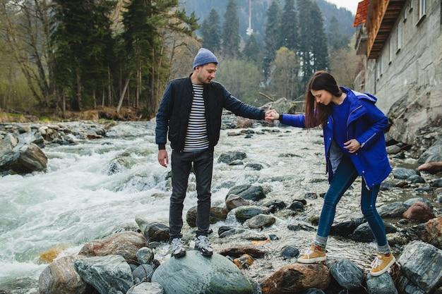 Jonge hipster mooie paar verliefd lopen op een rotsen aan de rivier in de winter woud