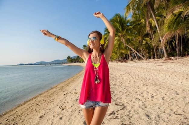 Jonge hipster mooie vrouw, tropisch strand, vakantie, kleurrijk, zomertrendstijl, zonnebril, koptelefoon, luisteren naar muziek, palmbomen achtergrond, glimlachen gelukkig, pret, details, close-up portret