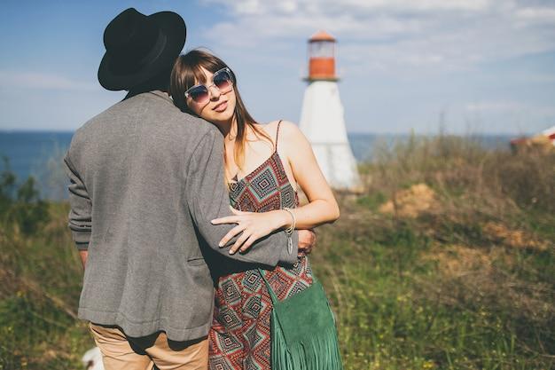 Jonge hipster paar indie stijl verliefd wandelen in platteland, vuurtoren op achtergrond