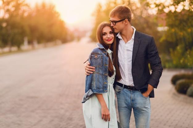 Jonge hipster paar verliefd buiten. prachtig sensueel portret van jonge stijlvolle mode paar poseren in de zomer zonsondergang. vrij jong meisje in jeansjasje en haar knappe vriend die lopen.