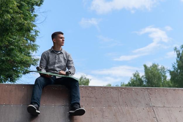 Jonge hipster-skateboarder zit op de basis van de skate-achtbaan in het park tegen de achtergrond van de zomerhemel en groene wazige bomen op een warme dag. kopieerruimte