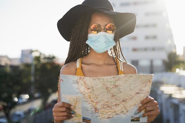 Jonge hipster-toeristenmeisje dat kaart buiten gebruikt terwijl ze een veiligheidsmasker draagt op reisvakantie - focus op gezicht