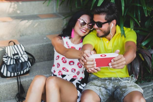 Jonge hipster verliefde paar, luisteren naar muziek op spreker, glimlachen gelukkig, plezier, zomer outfit, tropische vakantie, zonnebril