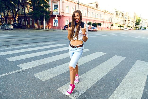 Jonge hipster vrouw gek en plezier hebben in het centrum van europa, wandelen en alleen reizen, vreugde, emoties, stijlvolle casual kleding en rugzak, zonnige heldere kleuren