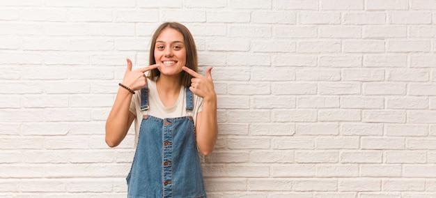 Jonge hipster vrouw glimlacht, wijzend op mond