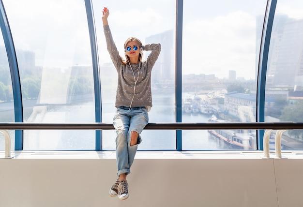 Jonge hipster vrouw in casual outfit plezier luisteren naar muziek in koptelefoon, spijkerbroek, trui en zonnebril dragen, stedelijke stijl zit bij raam met uitzicht op de stad