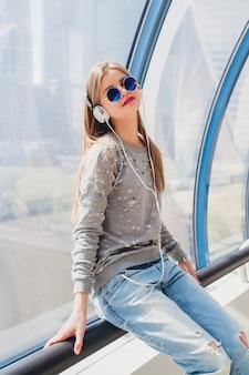Jonge hipster vrouw in casual outfit plezier luisteren naar muziek in koptelefoon, spijkerbroek, trui en zonnebril, stedelijke stijl