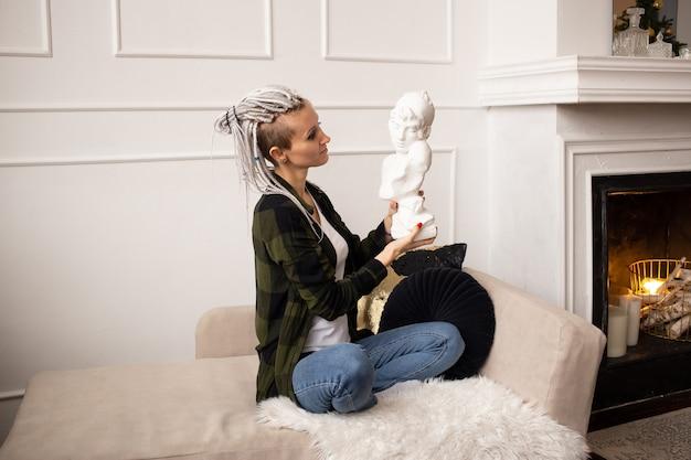 Jonge hipster vrouw in casual stijl met dreadlocks thuis op de bank met sculptuur