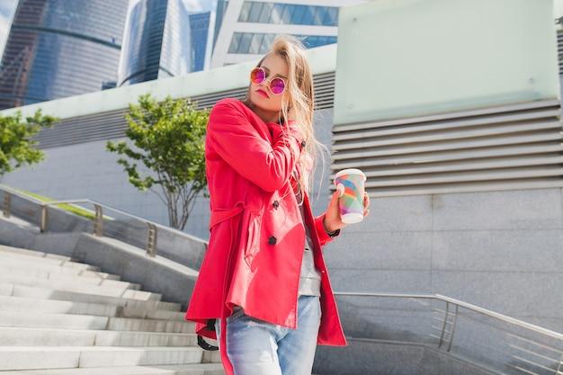 Jonge hipster vrouw in roze jas, jeans in straat met koffie luisteren naar muziek op de koptelefoon