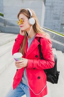 Jonge hipster vrouw in roze jas, jeans in straat met rugzak en koffie luisteren naar muziek op de koptelefoon