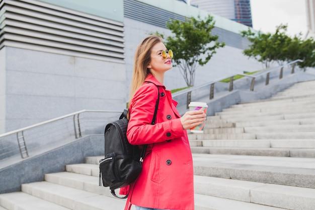 Jonge hipster vrouw in roze jas, jeans in straat met rugzak en koffie luisteren naar muziek op koptelefoon, zonnebril dragen