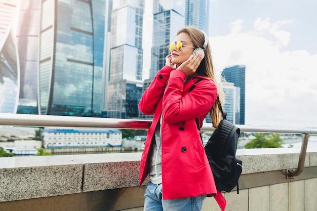 Jonge hipster vrouw in roze jas, jeans in straat met rugzak luisteren naar muziek op de koptelefoon