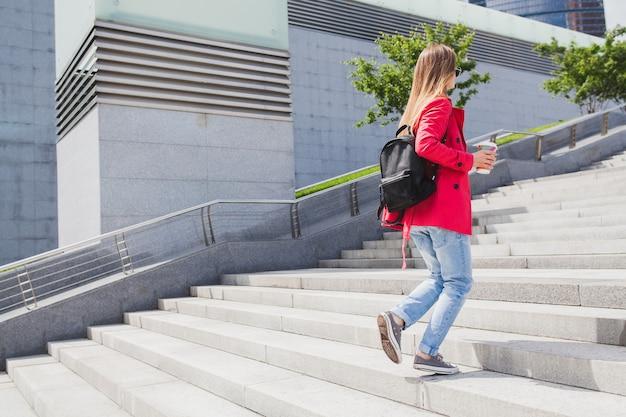 Jonge hipster vrouw in roze jas, jeans lopen op trappen in straat met rugzak en koffie luisteren naar muziek op koptelefoon, zonnebril dragen