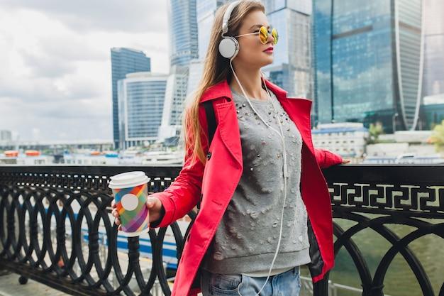 Jonge hipster vrouw in roze jas, jeans wandelen in straat met rugzak en koffie luisteren naar muziek op koptelefoon, zonnebril dragen