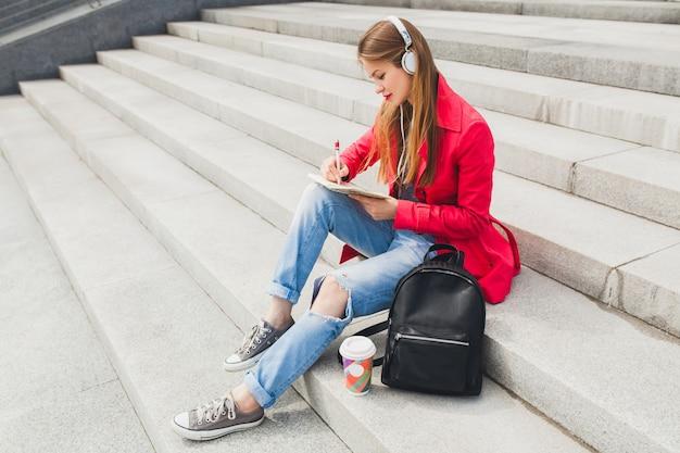 Jonge hipster vrouw in roze jas, jeans zitten in straat met rugzak en koffie luisteren naar muziek op de koptelefoon, student maken van aantekeningen