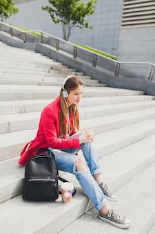 Jonge hipster vrouw in roze jas, jeans zitten in straat met rugzak en koffie luisteren naar muziek op de koptelefoon