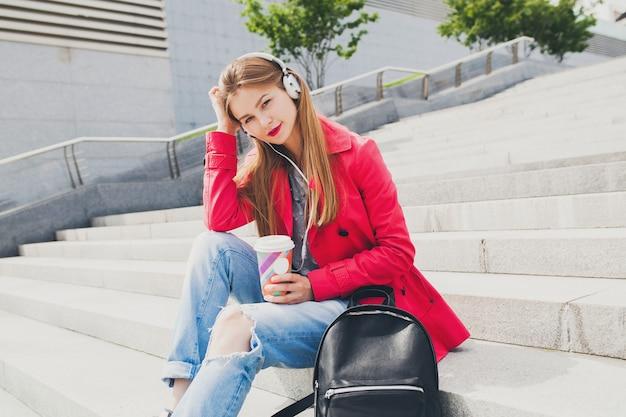 Jonge hipster vrouw in roze jas, jeans zitten in straat met rugzak en koffie luisteren naar muziek op koptelefoon, grote stad stedelijke lente stijltrend