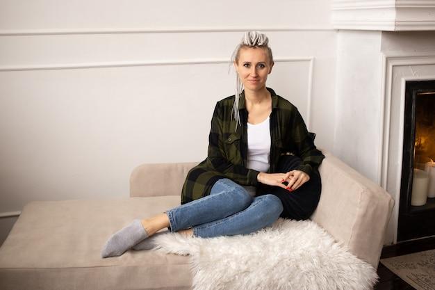 Jonge hipster vrouw met dreadlocks thuis zittend op de bank
