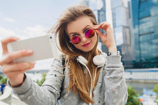 Jonge hipster vrouw plezier in straat, roze zonnebril dragen, lente zomer stedelijke stijl, selfie pisture nemen op smartphone