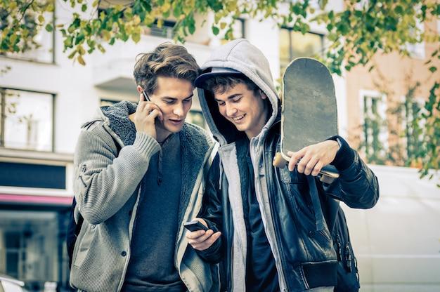 Jonge hipsterbroers die pret met smartphone hebben