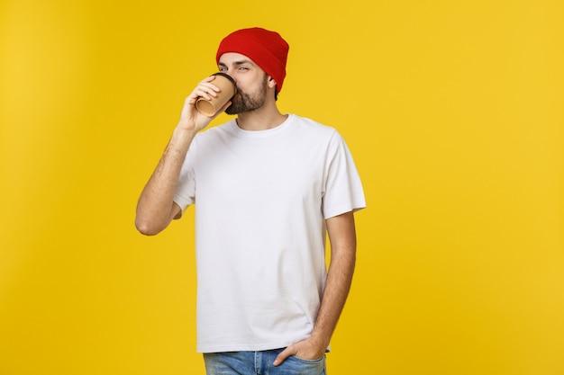 Jonge hipstermens die een kop van koffie houdt die over gele achtergrond wordt geïsoleerd