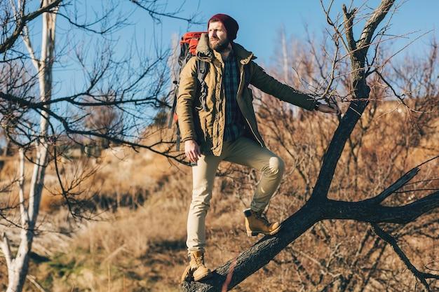 Jonge hipstermens die met rugzak in de herfstbos reist die een warme jas draagt