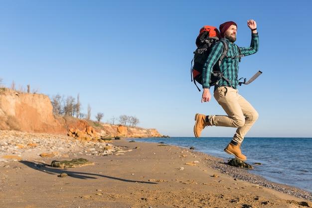 Jonge hipstermens die met rugzak reist in de herfstzeekust met een warme jas en muts?