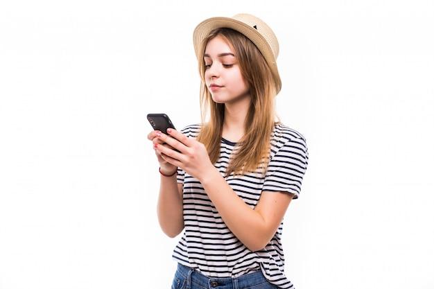 Jonge hipstervrouw in strohoed en zonnebril die mobiele telefoon over witte muur met behulp van