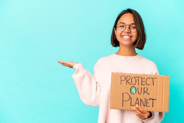 Jonge hispanic gemengd ras vrouw met een bescherm onze planeet karton met een kopie ruimte op een palm en met een andere hand op de taille.