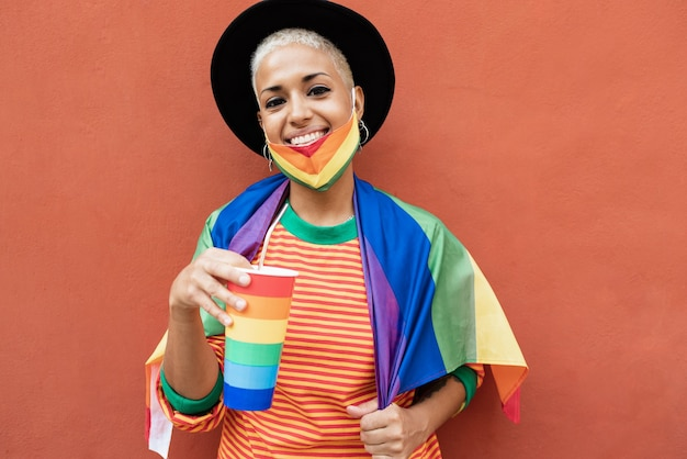 Jonge homovrouw drinkt uit een regenboogglas tijdens pride-evenement - focus on face