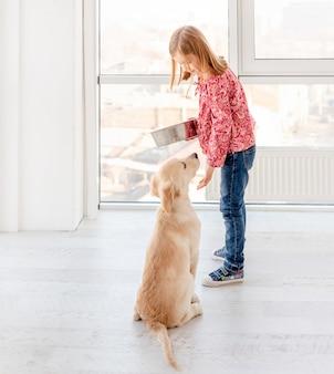 Jonge hond zit naast meisje