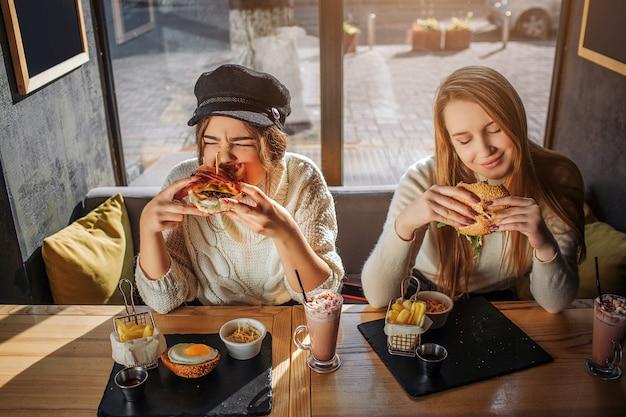 Jonge hongerige vrouwen zitten binnen aan tafel. ze eten hamburgers. modellen eten graag. zij vinden het leuk.