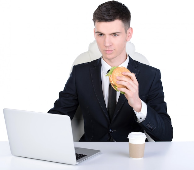 Jonge hongerige zakenman die hamburger eet.