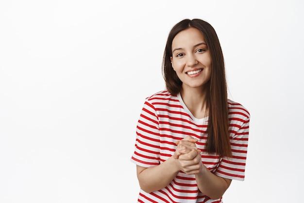 Jonge hoopvolle vrouw balde handen, glimlachend en kijkend naar de voorkant met vriendelijke beleefde gezichtsuitdrukking, wachtend op iets, om gunst vragen, witte muur.