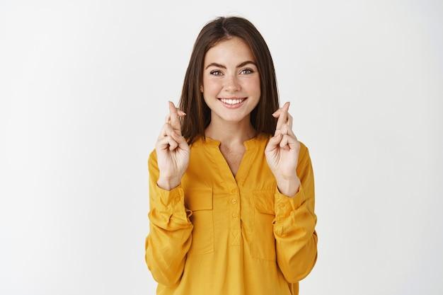 Jonge hoopvolle vrouw die een wens doet, staande met gekruiste vingers voor geluk, gele blouse dragen