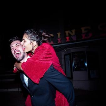 Jonge huilende man die op de rug gelukkig aantrekkelijke vrouw op straat