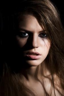 Jonge huilende vrouw op donkere achtergrond