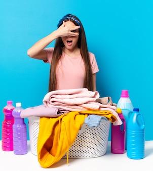 Jonge huishoudster die geschokt, bang of doodsbang kijkt en het gezicht bedekt met de hand