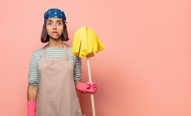 Jonge huishoudster die verbaasd en verward kijkt, lip bijt met een nerveus gebaar, niet wetend het antwoord op het probleem