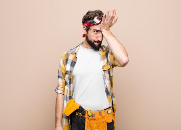 Jonge huishoudster man verhogen palm naar voorhoofd denken oeps, na het maken van een domme fout of herinneren, dom gevoel tegen vlakke muur