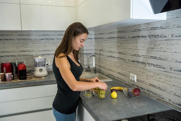 Jonge huisvrouw die fruit op een houten bord snijdt terwijl ze gezond voedsel maakt voor het ontbijt in de keuken